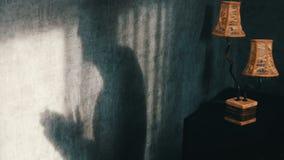 Uma sombra sinistra em uma sala escura gótico ao lado de uma lâmpada do amarelo do vintage, fricciona irritadamente suas mãos Gho filme