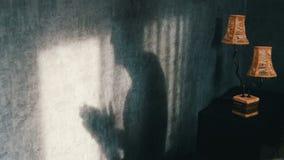 Uma sombra sinistra em uma sala escura gótico ao lado de uma lâmpada do amarelo do vintage, fricciona irritadamente suas mãos Gho video estoque