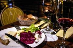 Uma tabela é ajustada com vinho, queijo, e pão Fotos de Stock