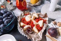 Uma tabela bonita com petiscos, mentiras do queijo com corintos vermelhos fotografia de stock