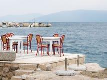 Uma tabela branca com as cadeiras vermelhas na frente do mar Fotografia de Stock