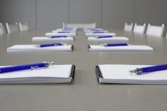 Uma tabela cinzenta com cadeiras cinzentas e colocação dos cadernos Imagem de Stock