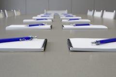 Uma tabela cinzenta com cadeiras cinzentas e colocação dos cadernos Imagem de Stock Royalty Free