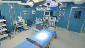 Uma tabela cirúrgica vazia e não utilizada sob o equipamento de trabalho próximo das luzes médicas 4K video estoque