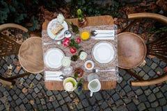 Uma tabela de café da manhã decorada com café, ovo cozido, suco de laranja e strudel no terraço exterior durante o outono Foto de Stock