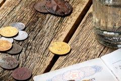 Uma tabela de madeira em que estão um vidro e as moedas da URSS com um bilhete militar do soldado Fotografia de Stock Royalty Free