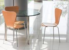 Uma tabela de vidro e cadeiras Imagens de Stock Royalty Free