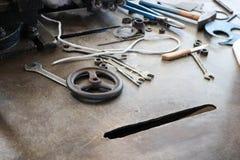 Uma tabela do ferro com uma ferramenta do trabajo em metal, chaves, martelos, chaves de fenda, pinças, facas, válvulas na fábrica fotografia de stock