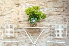 Uma tabela do jardim perto da casa Com um grande, ramalhete das flores fotografia de stock royalty free