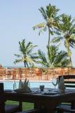 Uma tabela para dois povos perto de uma piscina com palmeiras Imagens de Stock