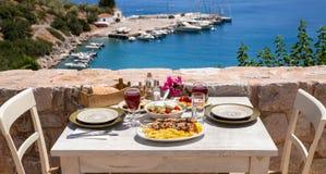 Uma tabela servida para dois com souvlaki e batatas fritas da galinha, salada grega, petiscos e bebidas no terraço do verão do ho Imagens de Stock Royalty Free