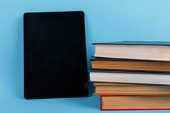 Uma tabuleta é ficada situada perto de uma pilha dos livros E Em um fundo azul imagem de stock