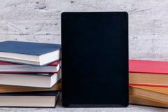 Uma tabuleta preta é encontrada entre muitos livros Em um fundo de madeira E fotografia de stock