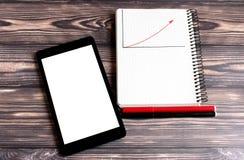 Uma tela branca em um portátil para seu texto, e um bloco de notas para escrever colocam em um fundo escuro Perto dos dois marcad fotos de stock royalty free