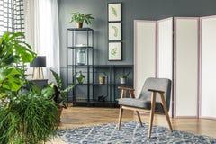 Uma tela decorativa ao lado das prateleiras pretas e atrás de um chai cinzento fotografia de stock