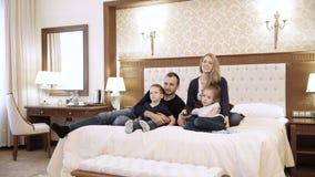 Uma televisão de observação da família feliz na sala de hotel que senta-se na cama vídeos de arquivo
