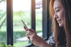 Uma terra arrendada asiática da mulher, usando e olhando o telefone esperto com fundo da natureza do verde do borrão fotografia de stock