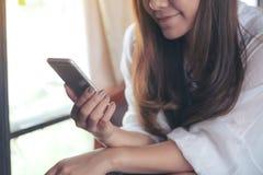 Uma terra arrendada asiática da mulher, usando e tocando em um telefone esperto fotos de stock royalty free