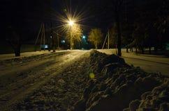 Uma tocha-luz inunda uma estrada encadernada da neve nocturna no outskir Fotos de Stock Royalty Free