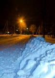 Uma tocha-luz inunda uma estrada encadernada da neve nocturna no outskir Fotos de Stock