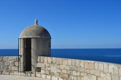 Uma torre de protetor de pedra que negligencia um mar azul Fotos de Stock Royalty Free