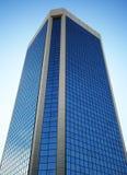 Uma torre de vidro alta reflete o céu fotografia de stock