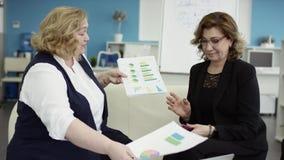 Uma trabalhadora com um plano de projeto para colegas em reunião, explicando ideias sobre o plano de voo para colegas de trabalho video estoque