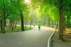 Uma trilha movimentando-se concreta do asfalt preto em um parque público, dois pessoas que vestem a camisa amarela e verde de T q foto de stock