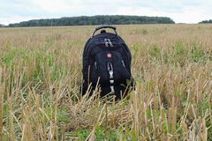 Uma trouxa pequena do turista está na terra no meio de um campo de inclinação Foto de Stock Royalty Free
