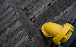 Uma tubulação amarela na plataforma de madeira de um navio Imagem de Stock