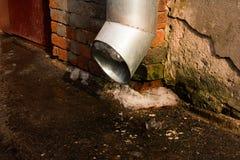 Uma tubulação de dreno com uma parte de gelo de derretimento na primavera na rua imagem de stock royalty free