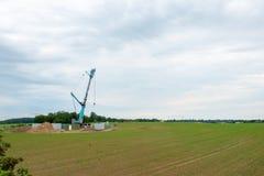 Uma turbina eólica é erigida com a ajuda de um grande guindaste foto de stock royalty free