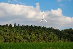 Uma turbina eólica está na floresta em Germany& x27; região de s Eifel Imagens de Stock