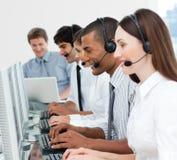 Uma unidade de negócio diversa com auriculares sobre Imagem de Stock Royalty Free