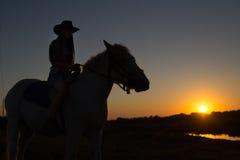 Uma vaqueira que monta um cavalo em um rancho é mostrada em silhueta contra o sol da tarde fotos de stock royalty free