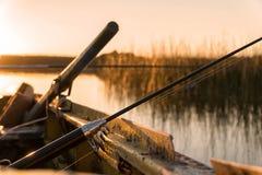 Uma vara de pesca quebrada encontra-se no lado do barco no por do sol fotografia de stock royalty free