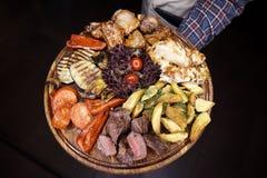 Uma variedade de carne cozida, peixe, vegetais em uma placa de madeira foto de stock