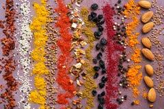 Uma variedade de especiarias em seguido em um fundo rústico roxo Fundo listrado da especiaria imagens de stock royalty free