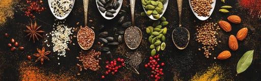 Uma variedade de especiarias, sementes, porcas nas colheres em um fundo rústico escuro Vista superior, configuração lisa imagens de stock royalty free