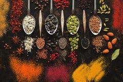 Uma variedade de especiarias, sementes, porcas nas colheres em um fundo r?stico escuro Vista superior, configura??o lisa fotografia de stock