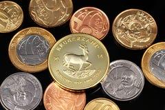 Uma variedade de moedas brasileiras em um fundo reflexivo preto com um sul - africano uma moeda do Krugerrand do ouro da onça imagem de stock royalty free