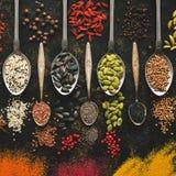 Uma variedade de sementes e de especiarias variadas nas colheres em um fundo escuro Vista superior, configuração lisa Especiarias imagens de stock royalty free