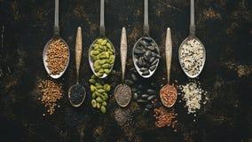 Uma variedade de sementes na colher no fundo escuro Configuração lisa, close-up Chia, linho, abóbora, girassol, coentro, sésamo,  fotografia de stock