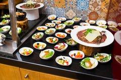 Uma variedade de variedades do queijo e guloseimas da carne com saladas e o outro fresco cortados imagem de stock royalty free