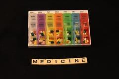 Uma variedade dos comprimidos em uma caixa semanal colorida do comprimido acima da medicina soletrou nas telhas em um fundo preto Fotos de Stock