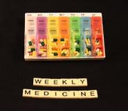 Uma variedade dos comprimidos em uma caixa semanal colorida do comprimido acima da medicina semanal soletrou nas telhas em um fun Imagem de Stock Royalty Free