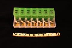 Uma variedade dos comprimidos em uma caixa semanal verde e branca do comprimido com medicamentação soletrou nas telhas em um fund Imagens de Stock Royalty Free