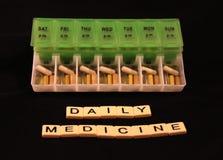 Uma variedade dos comprimidos em uma caixa semanal verde e branca do comprimido com medicina diária soletrou nas telhas em um fun Fotos de Stock Royalty Free