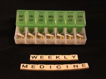 Uma variedade dos comprimidos em uma caixa semanal verde e branca do comprimido com medicina semanal soletrou nas telhas em um fu Fotos de Stock Royalty Free