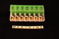 Uma variedade dos comprimidos em uma caixa semanal verde e branca do comprimido com medicina soletrou nas telhas em um fundo pret Foto de Stock Royalty Free